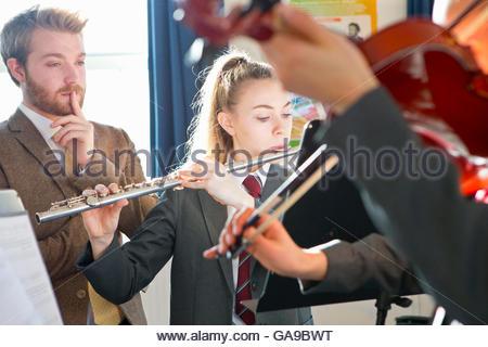 Lehrer unterrichten Schülerinnen und Schüler im Musikunterricht Querflöte und Geige zu spielen - Stockfoto
