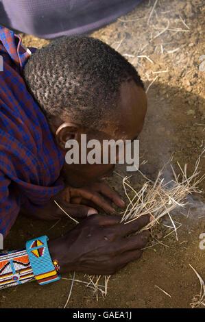 Masai Mann unter Feuer, Amboseli Nationalpark, Kenia, Afrika - Stockfoto