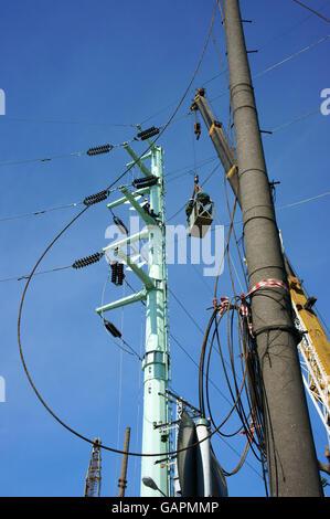 Elektriker arbeiten unter elektrischer Draht Netzwerk in den blauen ...