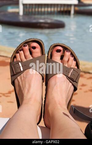Füße in Sandalen, lackierten Zehen, Sommerurlaub, Schwimmbad - Stockfoto