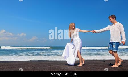 Glückliche Familie Flitterwochen Urlaub - nur verheiratet junger Mann und Frau laufen mit Spaß von schwarzen Sandstrand - Stockfoto