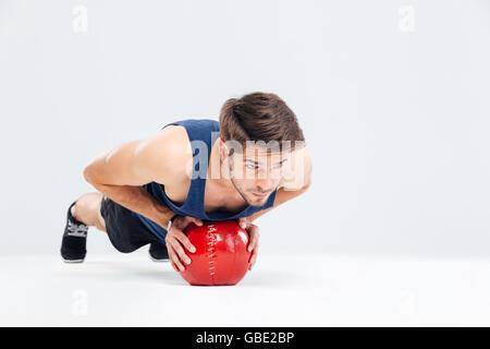 Sportler trainieren mit Fitness-Ball auf einem grauen Hintergrund isoliert - Stockfoto