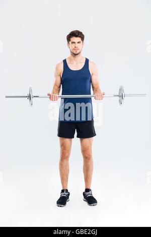 Junge Sportler Übungen für Bizeps mit Langhantel über weißem Hintergrund konzentriert - Stockfoto
