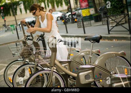 Eine Frau kehrt ihr Velib' Fahrrad, eine Docking-Station in Paris, Frankreich, 15. Juli 2007. - Stockfoto