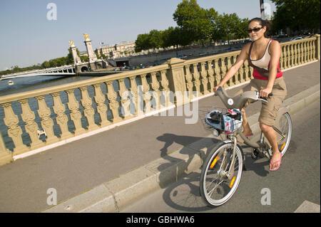 Eine Frau fährt eine Velib' Rad über die Pont des Invalides in Paris, Frankreich, 15. Juli 2007. - Stockfoto