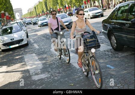 Ein Mann und eine Frau fahren ihre Velib' Fahrräder runter die Champs-Elysees in Paris, Frankreich, 15. Juli 2007. - Stockfoto