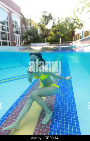Junge Frau, die im Wasser schwimmen - Stockfoto