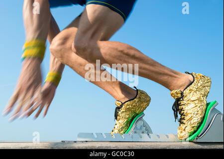 Sportler tragen gold Laufschuhe ausziehen in einer Unschärfe von aus den Startlöchern Race track - Stockfoto