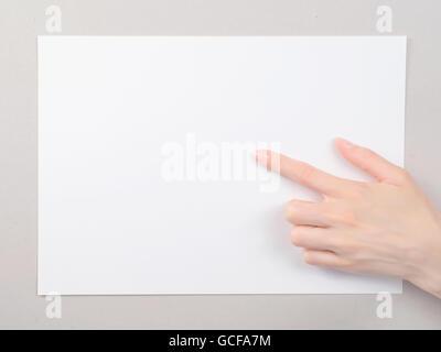Frau Fingerzeig auf das Blatt weißes Papier. Auf grauen Karton Hintergrund - Stockfoto
