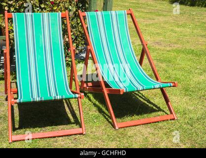 Zwei klappbare Liegestühle im Garten mit niemand sitzen. - Stockfoto