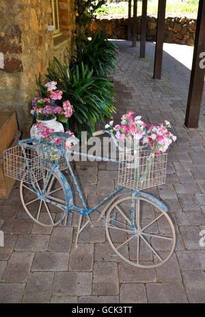 Shabby chic Fahrrad mit rustikalen blau-weiße Farbe und einen Metalldraht Korb mit Blumen auf Ziegel Bürgersteig - Stockfoto