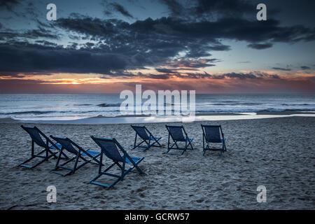 Sechs Liegestühle am Strand mit Sonne und Wellen - Stockfoto