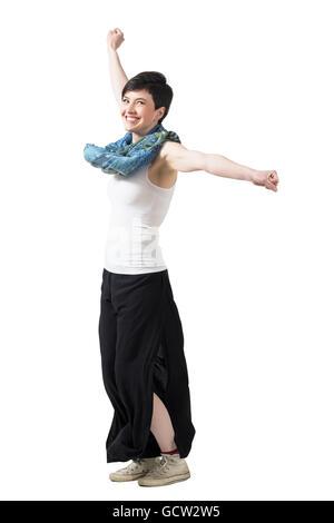 Fröhliche erregte Frau spinning mit erhobenen Armen tragen weite Hosen und Schal. Ganzkörper-Länge-Porträt über - Stockfoto