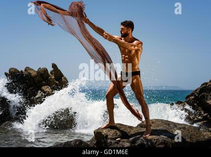 Ein muskulöser Mann in einem Badeanzug ein Netz ins Wasser stehend auf einem Felsen an der Küste zu werfen; Tarifa, - Stockfoto