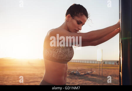 Schuss der muskulöse junge Frau trägt Sport BH stehen im Freien. Fitness Frauen eine Pause von der intensiven Arbeit. - Stockfoto