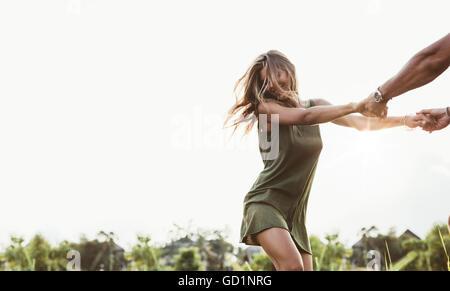 Schuss von attraktiven jungen Frau, die Hand in Hand des Mannes und der Tanz auf der Wiese. Paar genießt draußen - Stockfoto