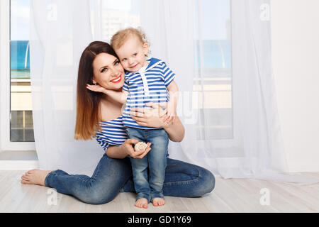 Junge Mutter und Tochter umarmt. Mutter und Tochter in einem gestreiften T-shirt gekleidet. Mutter hält eine Muschel. - Stockfoto