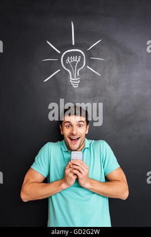 Fröhlich begeistert jungen Mann halten Smartphone und mit einer Idee über Tafel Hintergrund - Stockfoto