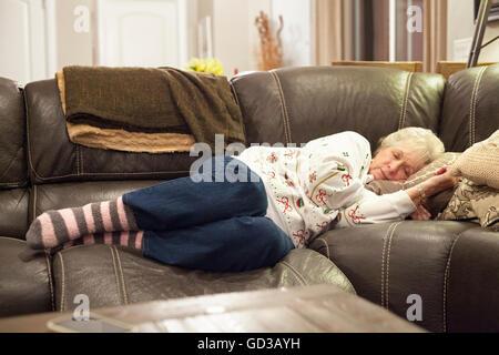 Eine graue dunkelhaarige Frau auf einem Sofa ein Nickerchen. - Stockfoto