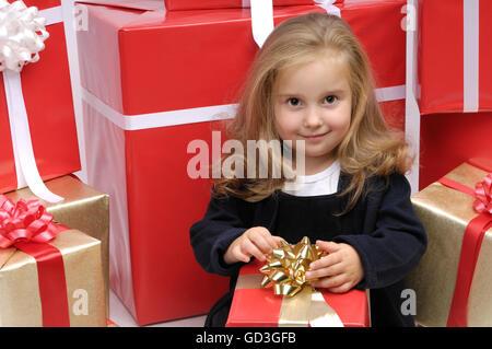 Glückliches kleine Mädchen sitzen umgeben von einem riesigen Haufen von Weihnachten Geschenk-Boxen - Stockfoto