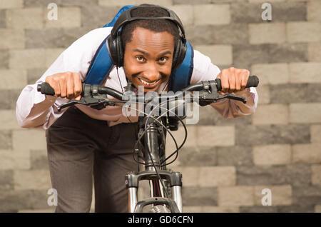 Mann trägt graue Büro Hosen, weiße rote Businesshemd und Rucksack mit dem Fahrrad im Rennsport Position lächelnd, - Stockfoto