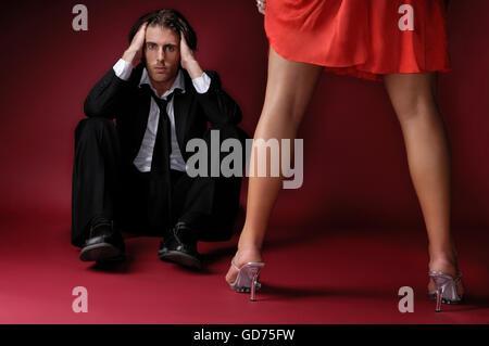Frau steht vor einem depressiven jungen Mann auf dem Boden sitzend - Stockfoto