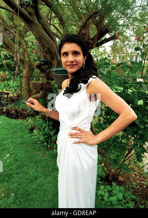 Attraktive junge Frau im smart weißen Ballkleid stehen im Garten bereit, zur Abendveranstaltung. - Stockfoto