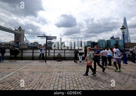 Touristen am Victoria Embankment London mit London Bridge The Shard und Rathaus auf die Skyline. - Stockfoto