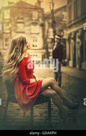 junge schöne blonde Frau sitzt auf dem Stuhl in der Mitte des gepflasterten Straße