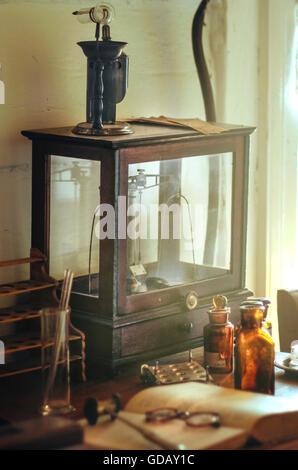 alten Zeiten Arztzimmer mit Arzneimitteln, Flaschen, Schrank, Buch und Brille - Stockfoto