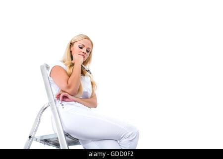 Eine schöne junge blonde Frau, die eine Pause vom malen und Standortwahl auf einer Leiter