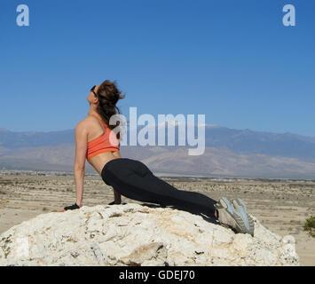Frau tut ein nach oben mit Blick auf Hund Yoga pose auf einem Felsen in der Wüste, Nevada, Amerika, USA - Stockfoto