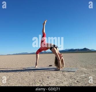 Frau tut eine einer vierbeinigen Rad-Pose in einem trockenen See, Nevada, America, USA - Stockfoto