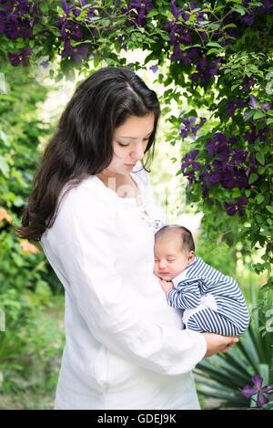 Mutter mit schlafenden Baby im Garten - Stockfoto
