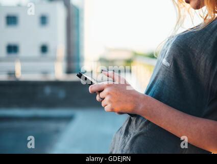 Frau, die in der Straße mit einem digitalen tablet - Stockfoto