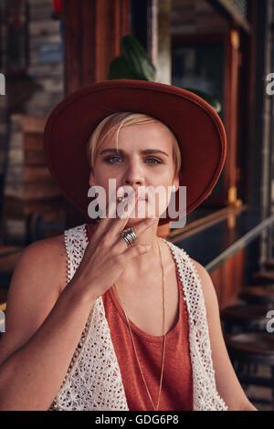 Porträt der jungen Frau mit Hut, rauchte eine Zigarette in einem Café. - Stockfoto