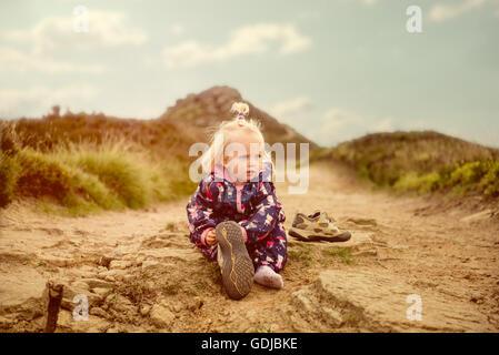Kleines Mädchen passt auf Mutters Schuhe auf einem Pfad in den Hügeln. - Stockfoto