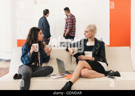 Frauen im Büro sitzen auf dem Sofa im Chat - Stockfoto
