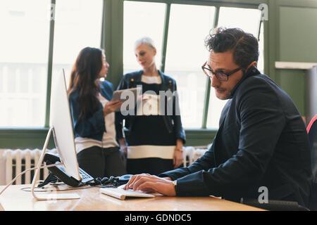 Mann mit Computer und Smartphone am Schreibtisch, Kollegen reden im Hintergrund - Stockfoto