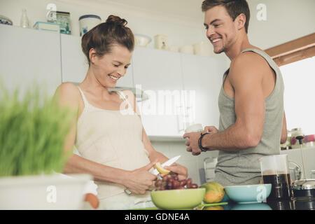 Junges Paar, lachen, während die Zubereitung von Frühstück am Küchentisch - Stockfoto