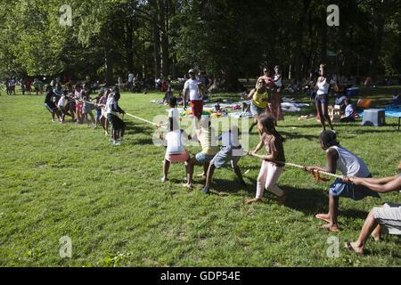Kinder und Eltern spielen Tauziehen bei einem Picknick im Prospect Park, Brooklyn, NY. - Stockfoto