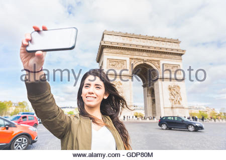 Junge Frau, die die Smartphone Selfie mit Arc de Triomphe, Paris, Frankreich - Stockfoto