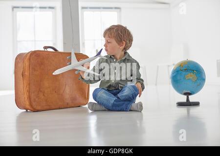 Junge sitzt auf Boden spielen mit Spielzeugflugzeug - Stockfoto