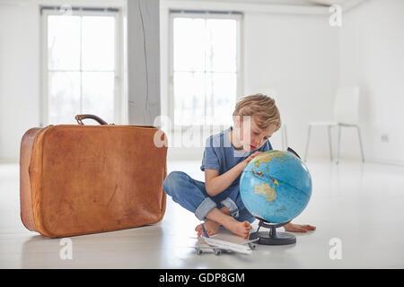 Junge auf Boden starrte auf Kugel sitzend - Stockfoto