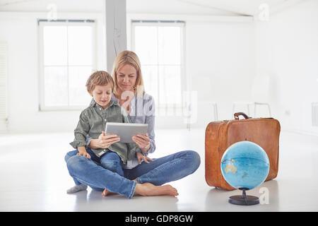 Reife Frau und Sohn sitzen auf Etage Blick auf digital-Tablette - Stockfoto