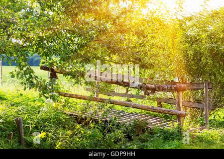 Traditionelle hölzerne Fußgängerbrücke überqueren Feld Graben - Stockfoto