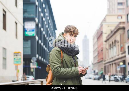 Junge Frau in der Straße stehen, hält smartphone - Stockfoto