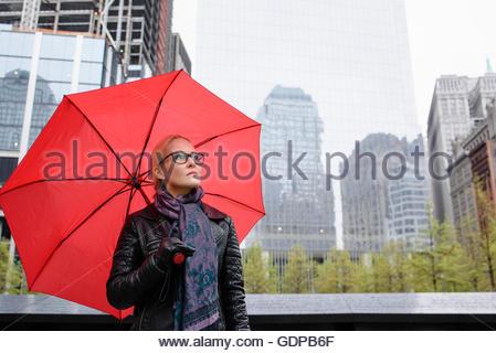 Weibliche Touristen mit roten Regenschirm Nachschlagen von One World Trade Center, New York, USA - Stockfoto