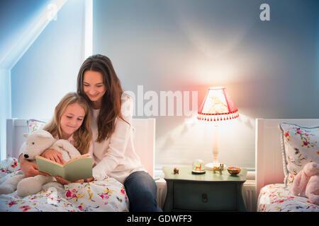 Mutter und Tochter Lesebuch im Schlafzimmer - Stockfoto