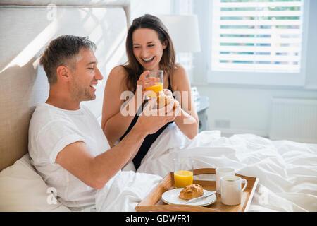 Lächelnde Paar genießt das Frühstück im Bett - Stockfoto